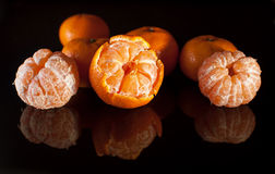 Grupp av mandariner med reflexion på svart bakgrund Fotografering för Bildbyråer