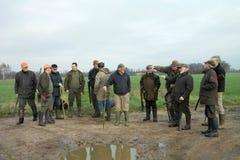 Grupp av manliga jägare som diskuterar var att gå därefter VinterNederländerna Jaktgrupp Arkivbild