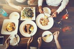 Grupp av manliga och kvinnliga vänner som har matställen och tillsammans äter biff och sallad och spagetti i restaurangen - bästa arkivbild