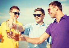 Grupp av manliga vänner som har gyckel på stranden Arkivbild