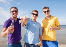 Grupp av manliga vänner med flaskor av öl Arkivfoton