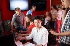 Grupp av massmediastudenter som arbetar i grupp för redigera för film royaltyfri fotografi