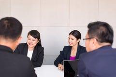 Grupp av meddela f?r folk f?r aff?r asiatiskt m?tande och arbetande, medan sitta p? rumkontorsskrivbordet tillsammans, teamworkbe royaltyfri foto