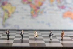Grupp av miniatyraffärsmän som går i schackbrädet Royaltyfri Bild