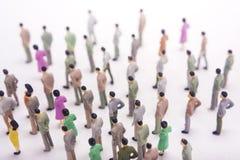 Grupp av miniatyrfolk över vit bakgrund Royaltyfri Fotografi