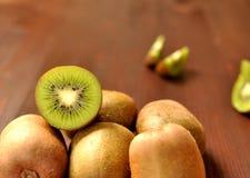 Grupp av mogen hel kiwi och halv kiwi på brun träbakgrund royaltyfria bilder