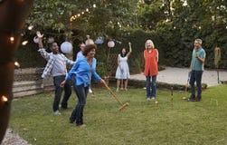 Grupp av mogna vänner som spelar krocket i trädgård tillsammans arkivbilder