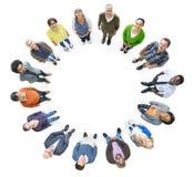 Grupp av multietniskt folk i en cirkel som ser upp Royaltyfri Foto
