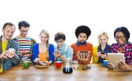 Grupp av multietniskt folk med Digital apparater royaltyfri fotografi