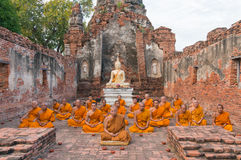 Grupp av munkar som sitter i förstörd byggnad av Wat Choeng Tha Temple Royaltyfria Foton