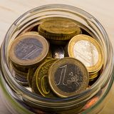 Grupp av mynt ett euro i en glass krus bank repet för anmärkningen för pengar för fokus hundra för euroeuros fem Arkivbild