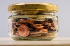Grupp av mynt och eurosedlar i en glass krus bank repet för anmärkningen för pengar för fokus hundra för euroeuros fem Arkivbilder