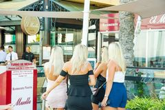 Grupp av nätta caucasian flickor för unga kvinnor med anseende för blont hår på ingången av restaurangen som diskuterar menyn arkivfoto