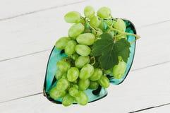 Grupp av nya mogna gröna druvor med ett blad i den glass vasen på gamla trävita plankor royaltyfria foton
