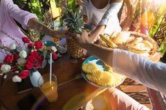 Grupp av oigenkännligt folk på hållande ananas för frukosttabell i händer tillsammans ung man och kvinna i morgon Arkivbilder