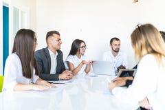 Grupp av olika affärsledare som rymmer ett möte runt om en tabell som diskuterar grafer som visar statistisk analys team arbete arkivbild