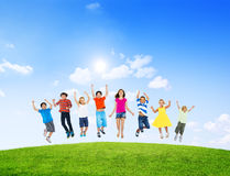 Grupp av olika barn som utomhus hoppar Arkivbilder