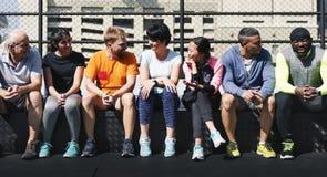 Grupp av olika idrottsman nen som tillsammans sitter arkivfoto