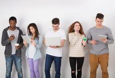Grupp av olika studenter som inomhus står i linje Arkivbilder