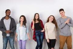 Grupp av olika studenter som inomhus står i linje Fotografering för Bildbyråer