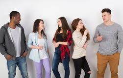 Grupp av olika studenter som inomhus står i linje Arkivfoton