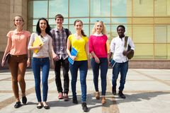 Grupp av olika studenter som tillsammans g?r fotografering för bildbyråer