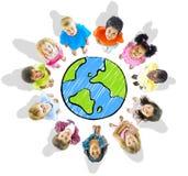 Grupp av olika ungar med jordklotet Fotografering för Bildbyråer