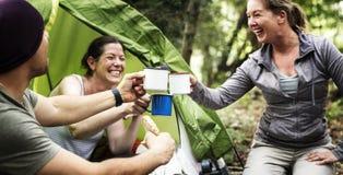 Grupp av olika vänner som campar i skogen royaltyfria bilder