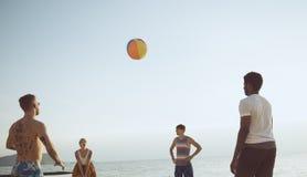 Grupp av olika vänner som spelar strandbollen tillsammans royaltyfria foton