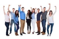 Grupp av olikt folk som lyfter armar Arkivfoton