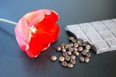 Grupp av orange rosor med mörka choklad- och kaffebönor på den gamla trätabellen Arkivfoton