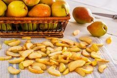 Grupp av päron och skivade päron på vita träbräden med en textilservett Royaltyfria Bilder