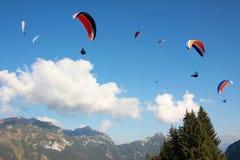 Grupp av paragliders i bergigt landskap Royaltyfri Foto
