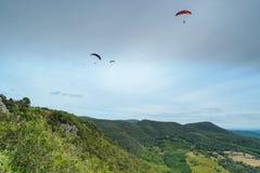 Grupp av paragliders ovanför berg royaltyfri foto
