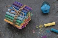 Grupp av pastellfärgade färgpennor, vässare, guling- och blåttfärgpennor åt sidan och pigmentdamm royaltyfri fotografi