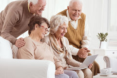 Grupp av pensionärer som använder bärbara datorn royaltyfri bild