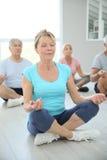 Grupp av pensionärer som gör meditationyoga royaltyfri bild