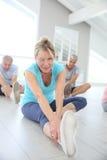 Grupp av pensionärer som gör yoga och att koppla av Arkivbilder