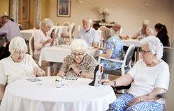 Grupp av pensionärer som spelar leken av bingoen i avgånghem royaltyfri bild