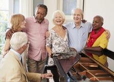 Grupp av pensionärer som står vid pianot och tillsammans sjunger arkivbilder