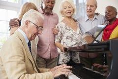 Grupp av pensionärer som står vid pianot och tillsammans sjunger arkivbild