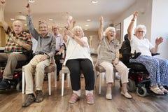 Grupp av pensionärer som tycker om konditiongrupp i avgånghem arkivbild