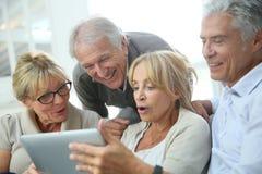 Grupp av pensionerat folk som har den roliga användande minnestavlan arkivfoto