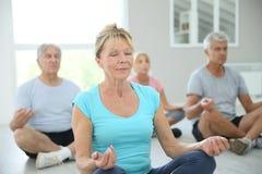 Grupp av pensionerat folk som kopplar av göra yogaexcercises Arkivfoto