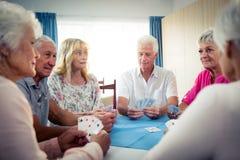 Grupp av pensionärer som spelar kort Royaltyfri Bild