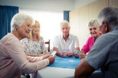 Grupp av pensionärer som spelar kort Fotografering för Bildbyråer