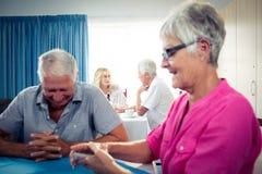 Grupp av pensionärer som spelar kort Arkivfoto
