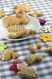 Grupp av pepparkakadjur och symboler på den vita plattan på rutig bordduk, två förälskade kaniner, jakt för påskägg arkivbilder