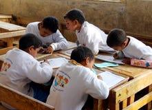 Grupp av pojkar i sammanträde för grupphandstilläxa på skrivbordet Royaltyfria Bilder