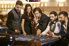 Grupp av poker för vänplayingroulette på en kasino royaltyfri foto